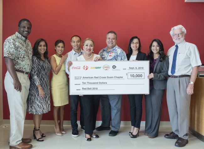 """The group of companies comprising Coca-Cola, Foremost, Subway, Chili's, and Glimpses of Guam donated $10,000 to the American Red Cross Guam Chapter for the signature fundraiser, ARC Red Ball, which has chosen for its 2018 iteration the theme, """"ARC Angels"""". Group Executive Vice President Marcos W. Fong (fourth from left), who also serves as chairman of the board of the American Red Cross Guam Chapter, leads the check presentation together with Sharleen Marchesseault (third from right), director of marketing strategy, Glimpses Advertising;  and Mike Brown (fourth from right), director of sales, Coca-Cola Beverage Co. (Guam), Inc. and Foremost Foods, Inc.  American Red Cross Guam Chapter CEO Chita A. Blaise (center) together with the Red Cross board of directors, from left, Karvin Flynn, Caroline Sablan, Anna Gera-Van Seters, Monica Duenas, and Jeff Cook accept the donation on behalf of the organization."""